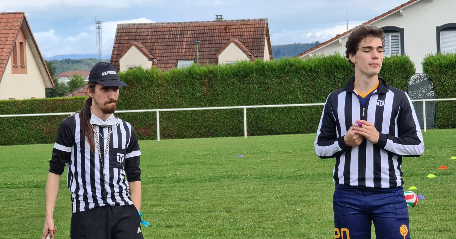 Deux personnes en maillot d'arbitres (rayures noires et blanches verticales) sur un terrain de sport en extérieur