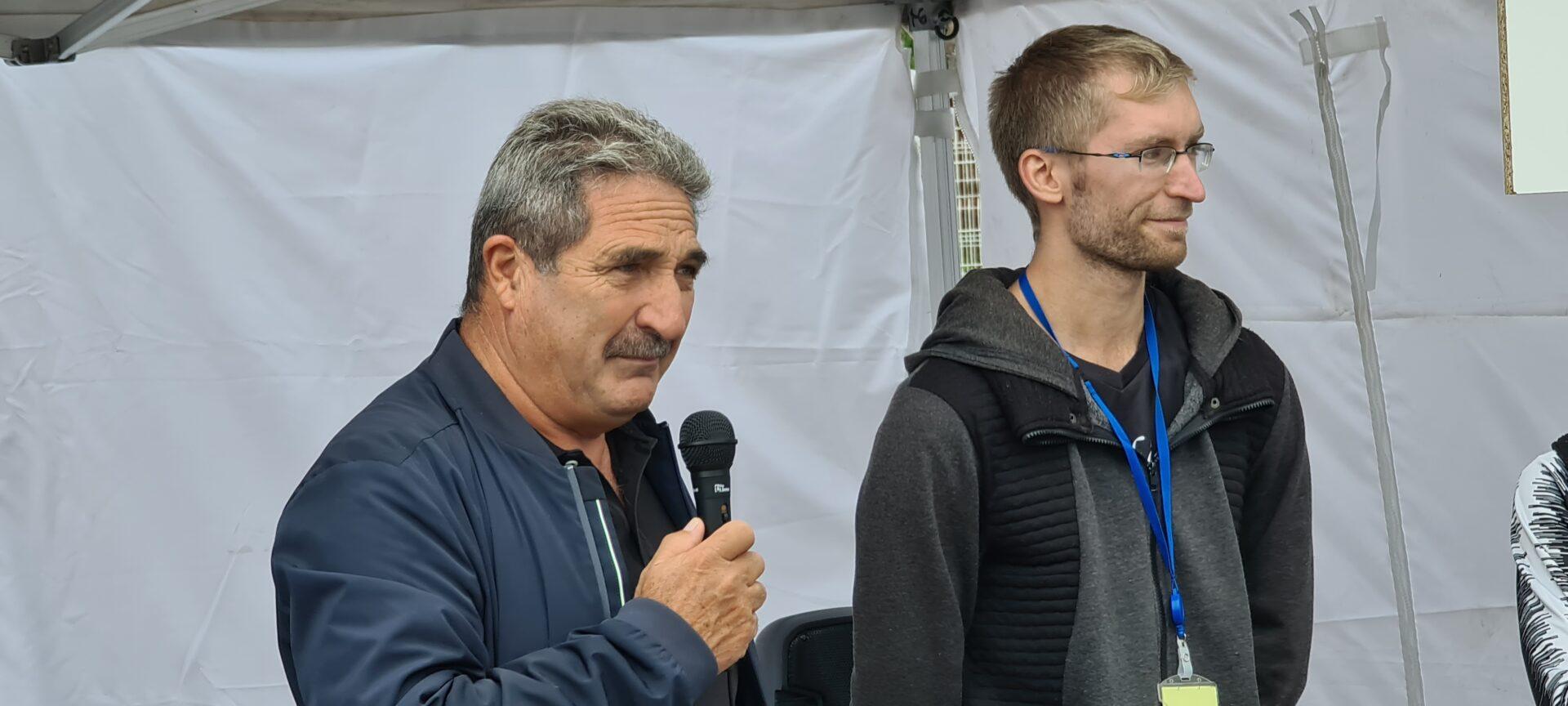 Homme aux cheveux gris tenant un micro à côté d'un autre plus jeune, blond avec des lunettes